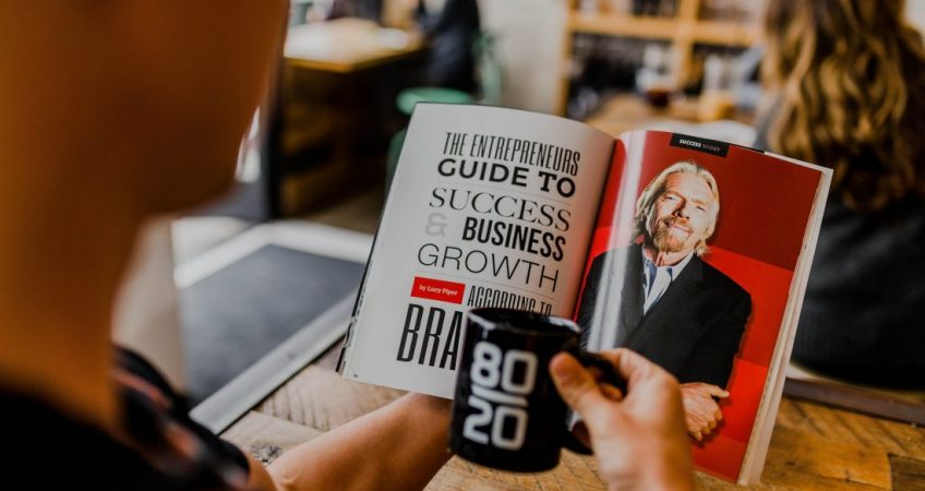 Man holding magazine article about investment and photo of Richard Branson